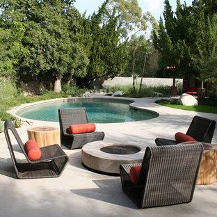 Diseño de piscina contemporánea, tipo riñón, con losas de hormigón