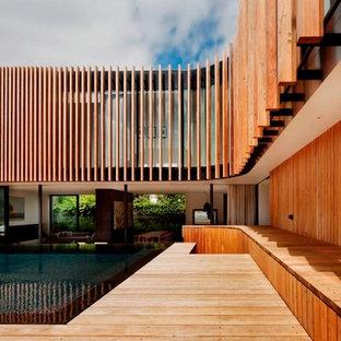 Immagine di una piscina contemporanea rettangolare dietro casa con fontane e pedane