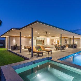Modelo de piscinas y jacuzzis alargados, minimalistas, de tamaño medio, rectangulares, en patio trasero, con adoquines de hormigón