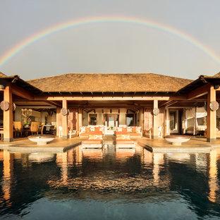 Foto di un'ampia piscina a sfioro infinito tropicale personalizzata dietro casa con una vasca idromassaggio e piastrelle