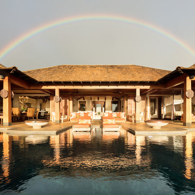 Hot tub - huge tropical backyard tile and custom-shaped infinity hot tub idea in Hawaii