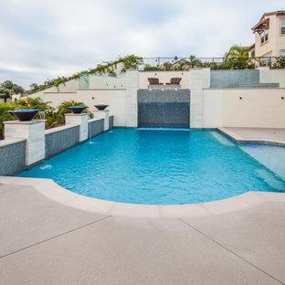 Modelo de piscina con fuente minimalista, de tamaño medio, rectangular, en patio trasero, con losas de hormigón