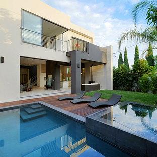Foto di una grande piscina minimal rettangolare dietro casa con una vasca idromassaggio e pedane