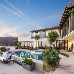 Tuscan backyard concrete and kidney-shaped hot tub photo in Los Angeles