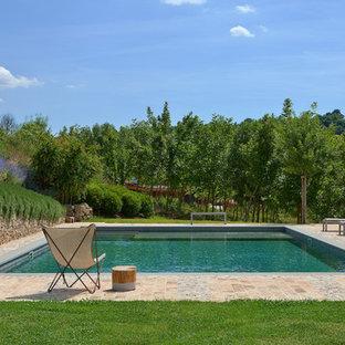 Ispirazione per una piscina mediterranea rettangolare di medie dimensioni con pavimentazioni in pietra naturale