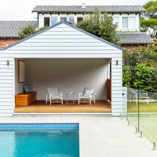 Beach style rectangular pool in Sydney with a pool house.