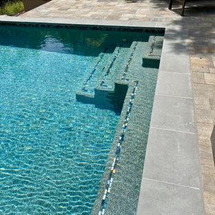 Réalisation d'un très grand couloir de nage arrière minimaliste rectangle avec un aménagement paysager autour d'une piscine et des pavés en béton.