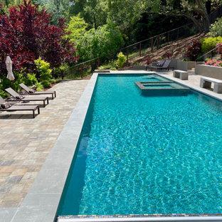 Diseño de piscina alargada, moderna, extra grande, rectangular, en patio trasero, con adoquines de hormigón