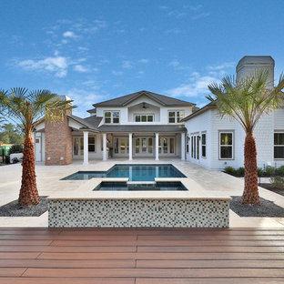 Foto de piscinas y jacuzzis costeros, grandes, en forma de L, en patio trasero, con adoquines de piedra natural