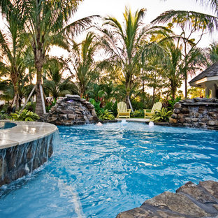 Mid-sized tropical backyard custom-shaped pool in Miami with a hot tub and natural stone pavers.