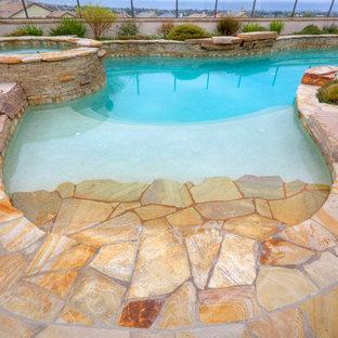 Diseño de piscinas y jacuzzis alargados, de estilo americano, grandes, a medida, en patio trasero, con adoquines de piedra natural