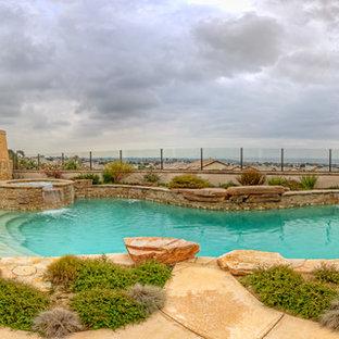 Imagen de piscinas y jacuzzis alargados, de estilo americano, grandes, a medida, en patio trasero, con adoquines de piedra natural