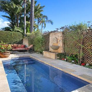 Kleiner Mediterraner Pool hinter dem Haus in rechteckiger Form mit Wasserspiel und Natursteinplatten in Orange County