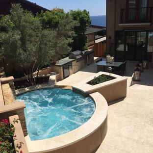 Ejemplo de piscina con fuente elevada, actual, pequeña, a medida, en patio trasero, con losas de hormigón