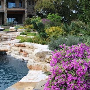 Diseño de piscina con fuente alargada, clásica renovada, de tamaño medio, redondeada, en patio trasero, con adoquines de piedra natural