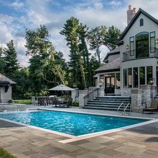 Ejemplo de piscinas y jacuzzis alargados, tradicionales, de tamaño medio, rectangulares, en patio trasero, con adoquines de piedra natural