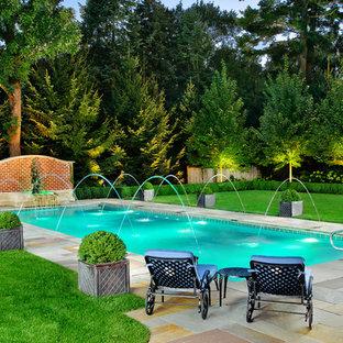 Foto de piscina con fuente alargada, clásica, de tamaño medio, rectangular, en patio trasero, con adoquines de piedra natural