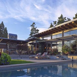 Foto de piscina alargada, actual, grande, rectangular, en patio trasero, con adoquines de hormigón