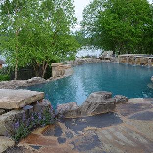 Geräumiger Klassischer Infinity-Pool hinter dem Haus in individueller Form mit Wasserspiel und Natursteinplatten in Sonstige