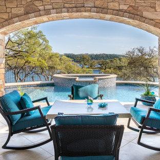 Diseño de piscina con fuente natural, actual, extra grande, a medida, en patio trasero, con suelo de baldosas