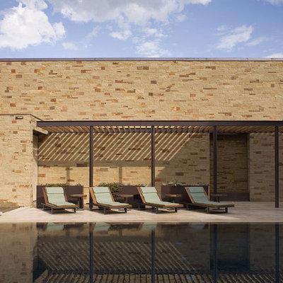 Large trendy courtyard tile and rectangular infinity pool photo in Austin