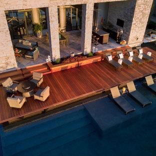 Ejemplo de piscina infinita, actual, a medida, en patio trasero, con entablado