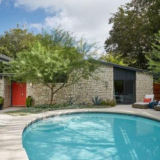 Imagen de piscina ecléctica, grande, en patio delantero, con suelo de baldosas