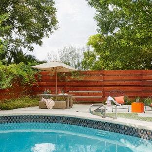 Diseño de piscina ecléctica, grande, en patio delantero, con suelo de baldosas