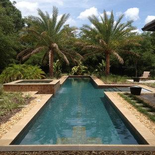 Imagen de piscina alargada, tropical, grande, rectangular, en patio trasero, con gravilla