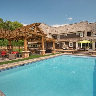 Idee per un'ampia piscina monocorsia tradizionale rettangolare dietro casa con una dépendance a bordo piscina e pedane