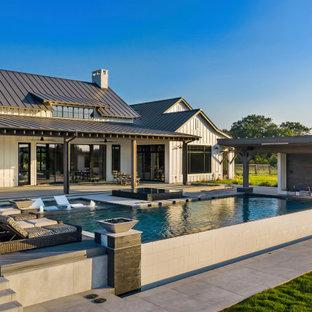 Ispirazione per una grande piscina a sfioro infinito country rettangolare dietro casa con pedane