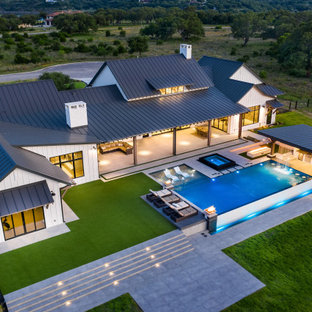 Foto di una grande piscina a sfioro infinito moderna rettangolare dietro casa con pedane