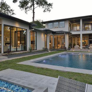Diseño de piscina con fuente alargada, contemporánea, grande, rectangular, en patio trasero, con losas de hormigón