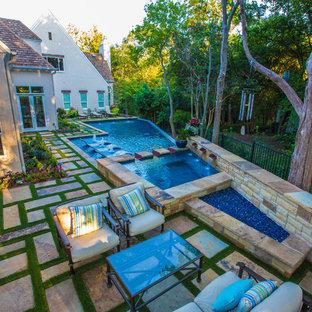 Ejemplo de piscinas y jacuzzis alargados, actuales, extra grandes, a medida, en patio trasero, con adoquines de piedra natural