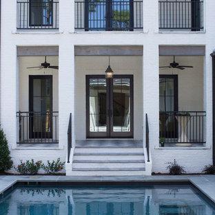 Imagen de piscina de estilo de casa de campo, grande, rectangular, en patio trasero, con suelo de baldosas