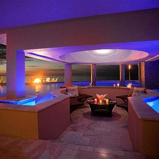 Ejemplo de piscina con fuente exótica, grande, a medida, en patio trasero