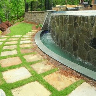 Diseño de piscina con fuente infinita, de tamaño medio, redondeada, en patio trasero