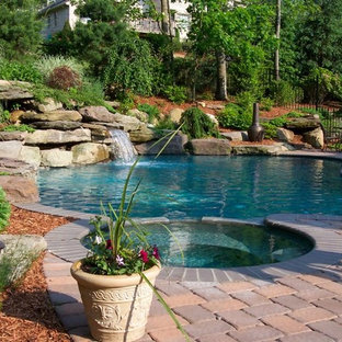 Design ideas for an expansive country backyard custom-shaped natural pool in New York with a water feature and brick pavers.
