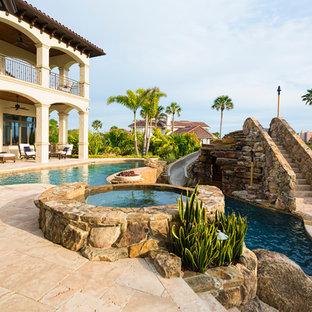 Diseño de piscina con tobogán natural, mediterránea, grande, en patio trasero