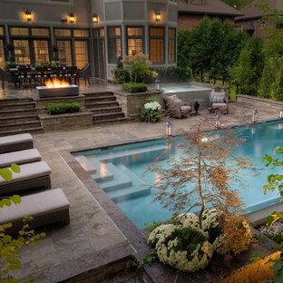 Diseño de piscina tradicional renovada, grande, rectangular, en patio trasero, con adoquines de piedra natural
