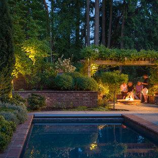 Ejemplo de piscina alargada, clásica, grande, rectangular, en patio trasero, con adoquines de ladrillo