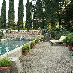 Modelo de piscina con fuente alargada, mediterránea, de tamaño medio, rectangular, en patio trasero, con gravilla