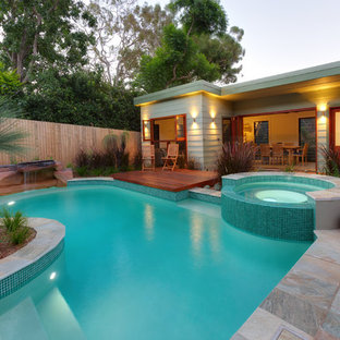 This is an example of a contemporary backyard custom-shaped pool in Sydney with a hot tub and natural stone pavers.