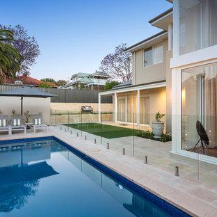 Modelo de piscina alargada, tradicional renovada, rectangular, en patio trasero, con suelo de baldosas