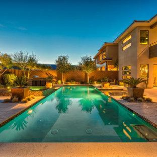 Diseño de piscinas y jacuzzis alargados, tropicales, grandes, rectangulares, en patio trasero, con adoquines de piedra natural