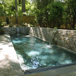 Small contemporary back rectangular lengths swimming pool in DC Metro with natural stone paving.