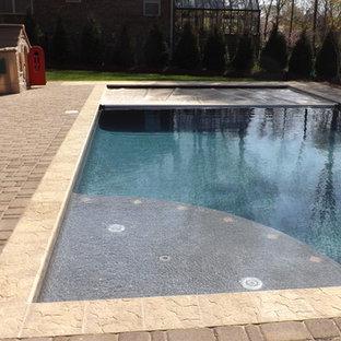Ejemplo de piscina con fuente alargada, clásica renovada, grande, rectangular, en patio trasero, con adoquines de ladrillo
