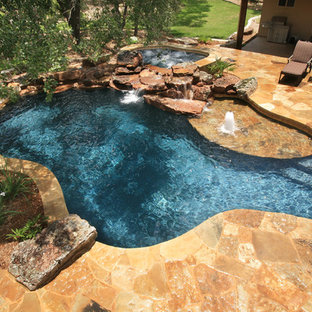 Mid-sized mountain style backyard stone and custom-shaped natural hot tub photo in Austin