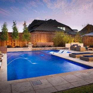 """Foto di una piscina minimalista a """"L"""" di medie dimensioni e dietro casa con fontane e pedane"""