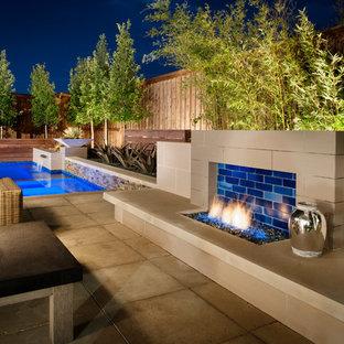Modelo de piscina con fuente minimalista, de tamaño medio, en forma de L, en patio trasero, con entablado